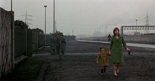 Giuliana (Monica Vitti) loopt in Il deserto rosso (1964) met naar zoontje naar de fabriek van haar man.