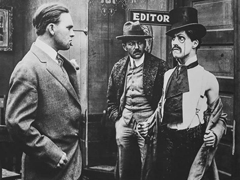 Charlie Chaplin (rechts) als oplichter voor het eerst op het witte doek in de korte film Making a Living (1914) van Keystone Studios.